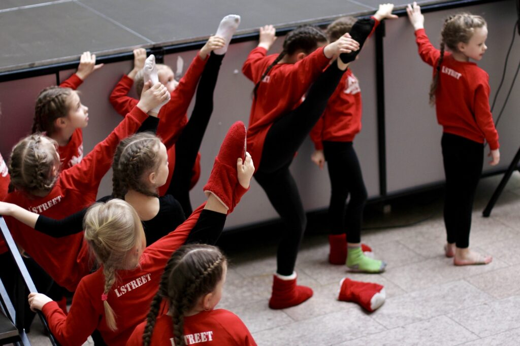 Young little girls in sportive wear stretch before a dance competition. Sport, health, training.
